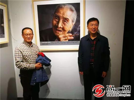 省老年保健协会张义昌会长(右)省老摄协蒋志舟主席(左,照片拍摄作者)在常德桃源百岁老人姜萍清(113岁)《风采依旧》作品前合影。