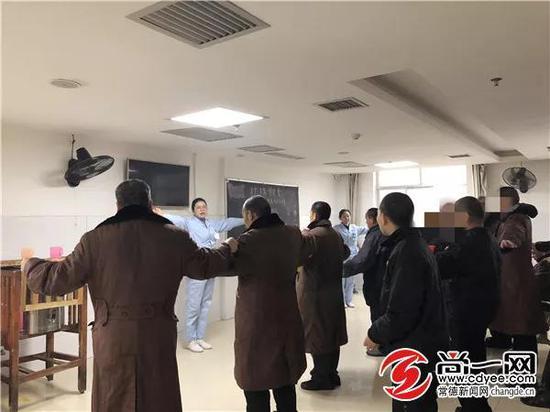 市康复医院一病室活动室内,护师张伟君正在带领男区滞留人员跳操。