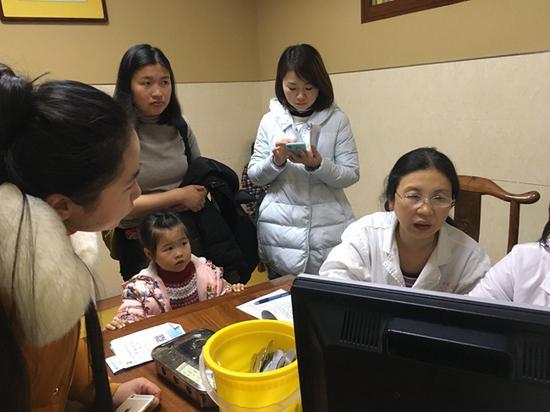 儿科医生正在为患儿看诊,焦急的家长等候挤满了诊室。胡翠娥 摄