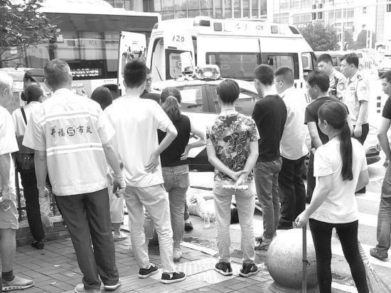 7月1日,长沙营盘路与便河边巷交会处,年轻男子醉卧街头,很多市民围在男子身边。图/受访者提供