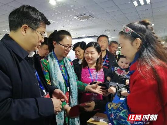 传承人何娟(右一)为参观者讲解大布江拼布绣参展作品文化知识。