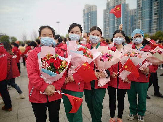 临行前,湖南医疗队队员收到群众的鲜花和祝福。