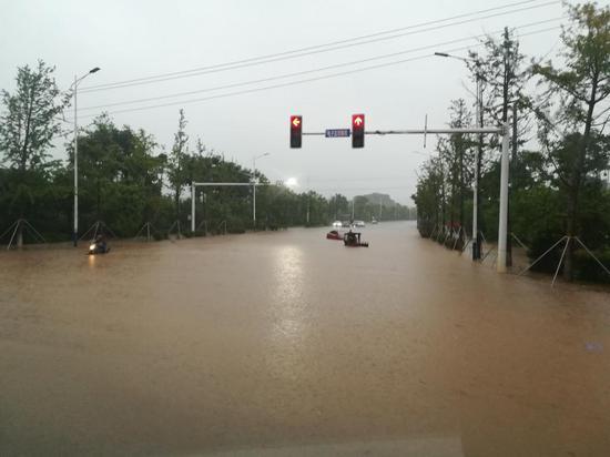 宁乡一红绿灯路口被淹,两车在水中熄火消防员解救三人