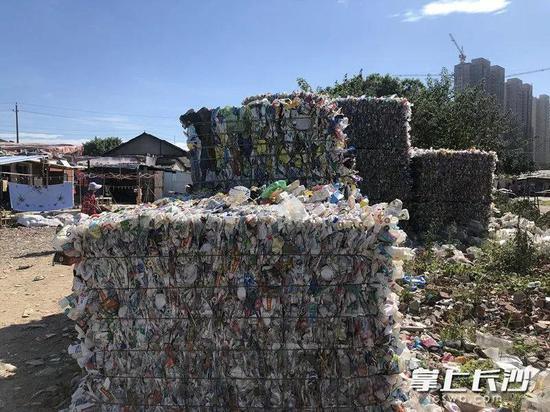 起火的废品回收处理厂,有大量被压缩处理的塑料瓶。