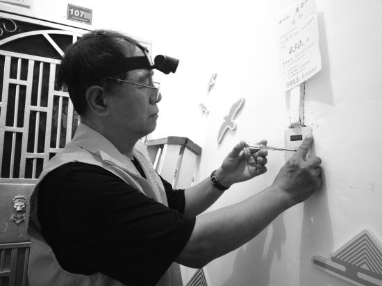8月29日上午,东湖社区居民陈树冬在社区3片12栋4单元的楼道内整修开关。图/记者满延坤