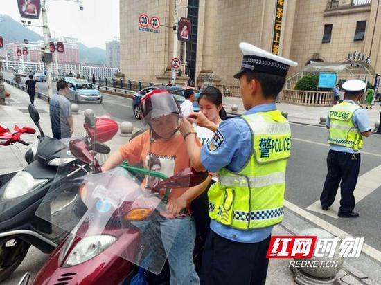 交警检查模特车车主安全帽佩戴情况。