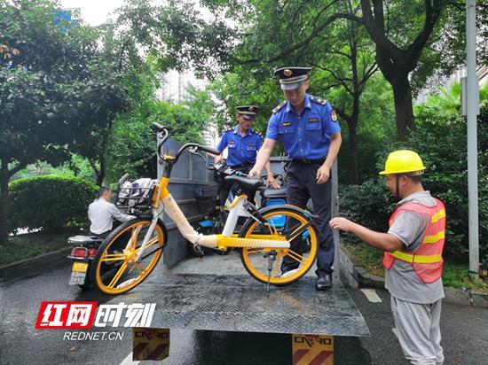 执法队员清运违规停放的共享单车。
