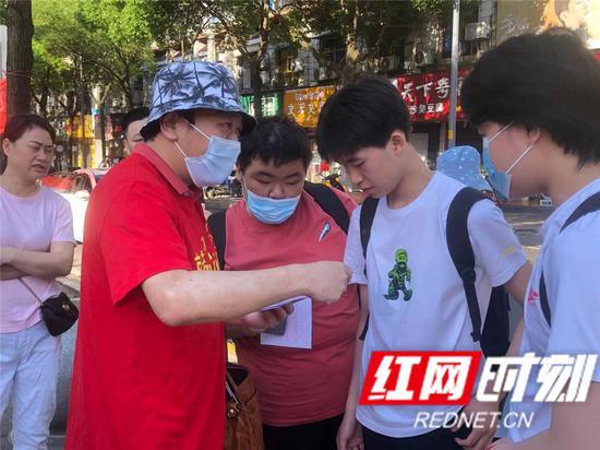 在岳阳市外国语学校考点,送考老师正在细心嘱咐孩子们注意事项。