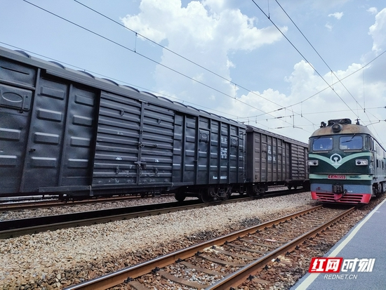 一辆满载货物的货运火车正在经过小站,从湖南出发,驶向广东方向