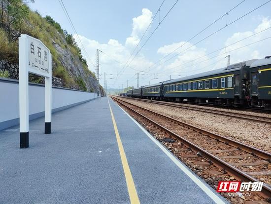 一辆绿皮火车正经过小站,满满的年代感