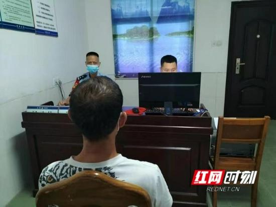 民警对男子进行审讯。