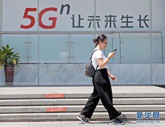 在北京西单,一名女子从一块5G广告牌前走过(6月3日摄)。 新华社记者才扬摄
