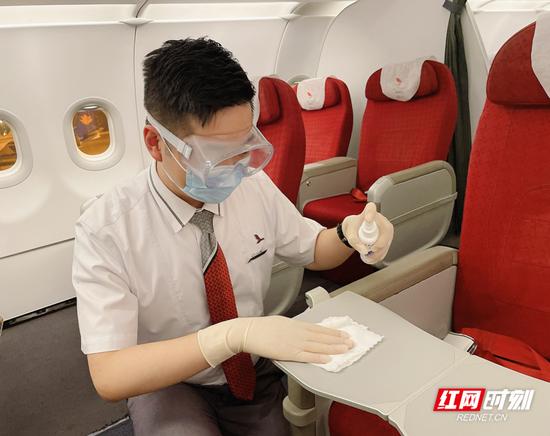 湖南航空乘务员在客舱进行消毒。