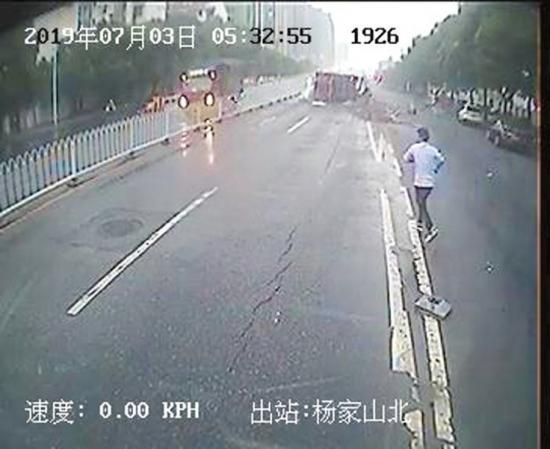 502路公交司机汤师傅将车停在了安全区域,快速跑到货车旁救人。   视频截图