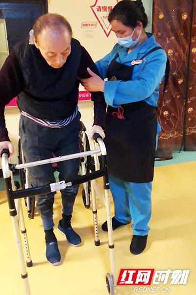 3月16日,康乃馨老年呵护中心综合区内,候建湘老人在护理员的搀扶下进行行走训练。