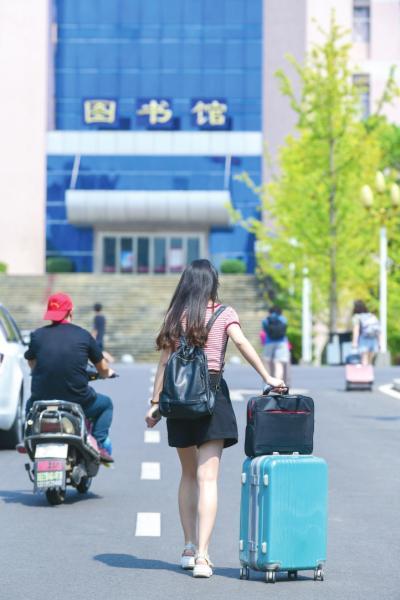 返校的学生在校园的道路上行走。