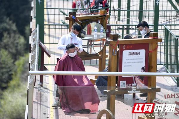 在景区内,理发师为游客和复工员工理发