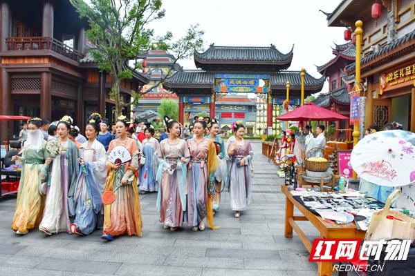 """5月1日至3日,长沙方特东方神画推出""""华裳盛典"""",图为游客着华服逛古风市集。何超 摄"""