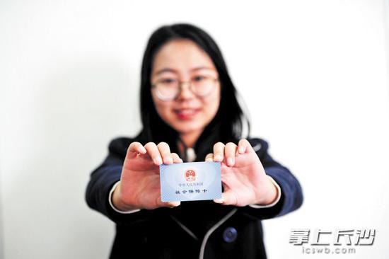"""如今的社保卡正不竭升级为可以当身份证、银行卡、诊疗卡、借书卡等等的""""便民卡""""。 长沙晚报记者 王志伟 摄"""