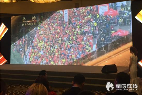 (与会人员共同观看长沙国际马拉松赛盛况。)