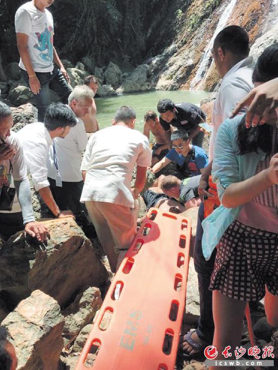 经过潘凯华(穿蓝色T恤者)等人施救,溺水青年终于有了自主呼吸,大家正准备抬溺水者上担架。沈曼平 摄