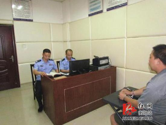 民警对嫌疑犯李某运进行审讯。