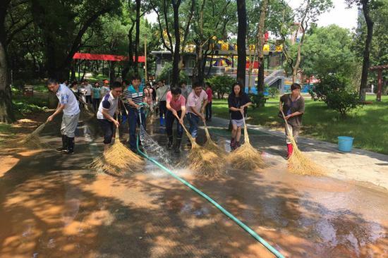(工作人员对路面进行清洗和消毒。)