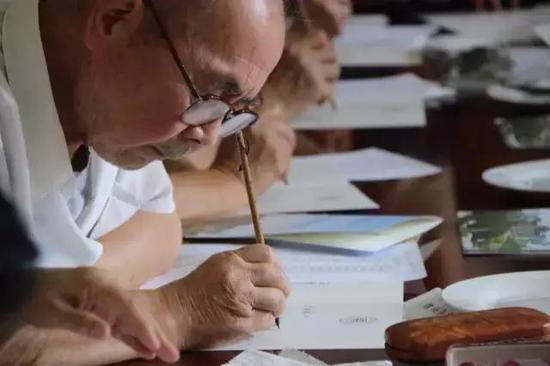 在参与今年书写毛笔通知书的老师中,文占申教授年龄最长,85岁高龄仍坚守在书写的书案前。