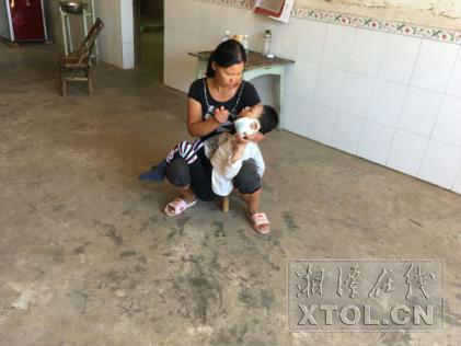 母亲陈灿辉给儿子陈健喂水(记者 刘崇婉 摄)