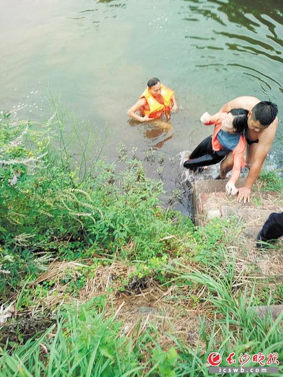 →罗智辉(穿救生衣)和李寄(赤膊)合力将女子救上岸。