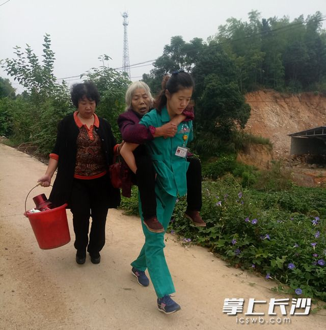 宁乡县中医医院的120急救医生刘畅背起患者赶山路。 (图片来自网络)