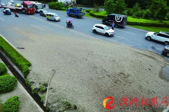 货车在东湖立交上侧翻,所运砂石倾泻在桥下的株洲大道上(记者 谢慧 摄)