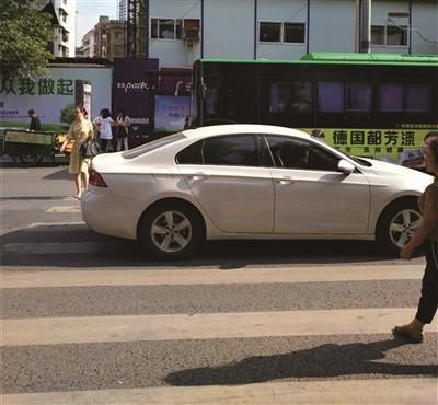 斑马线直通公交车站台,行人在车流中小心翼翼地走。 肖燕 摄