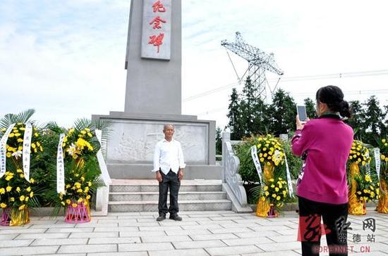戴修文的长孙戴万兴和孙女戴彩映在纪念碑前拍照留念。
