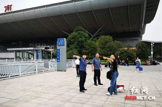 雨花区交通局武广科工作人员在站区巡查,为旅客指引道路。