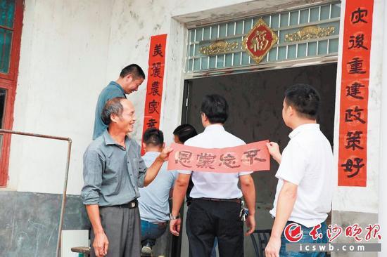 杨东木(左一)在新房贴上大家送来的对联。长沙晚报通讯员 刘静 摄
