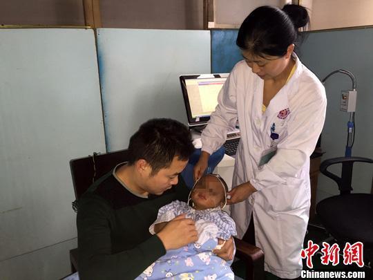 男童在爸爸的怀里做脑电图。湖南省人民医院 供图
