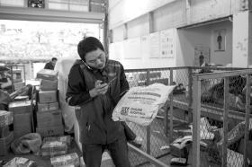 11月13日,杨宏亮在公司内分拣包裹时,接到了客户的催单电话。 组图/记者陈正