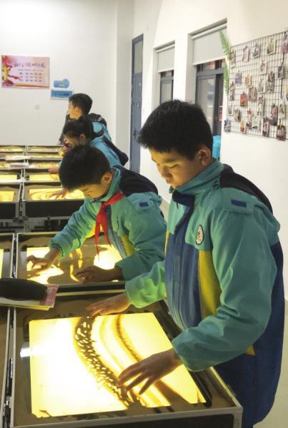 2月18日,长沙开福区浏阳河小学,学生正在上沙画课。图/受访者提供
