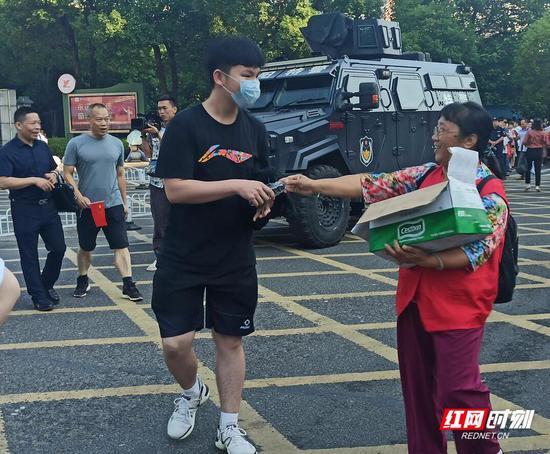 衡阳市一中考场外,志愿者正在给考生发矿泉水。