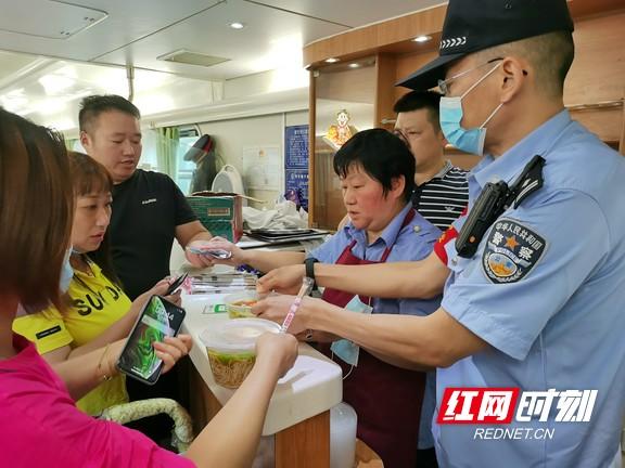 孙宏伟(右一)协助餐车工作人员为乘客分发餐食。