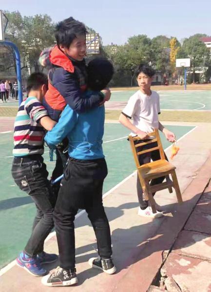 株洲市渌口区龙船镇中心学校,同学抱着刘念旭,带他到室外上课。 图/受访者提供