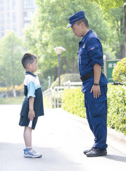 △ 8 月 31 日,长沙市实验小学梅溪湖学校,一年级新生正在向消防队员学习站姿。图 / 记者谢长贵