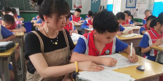 ▲近日,邵阳市西直街小学,妈妈李清萍正在陪患有脑偏瘫的儿子小杰上课。图 / 受访者提供