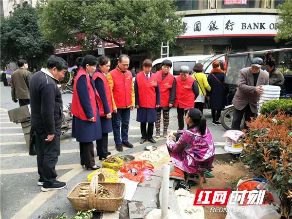 """石鼓区潇湘街道司前社区""""衡阳群众""""志愿者劝导商贩在规定的范围内摆放商品,不占道经营。"""
