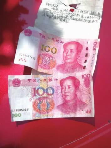肇事者留下的纸条和现金。 记者 李成辉 摄