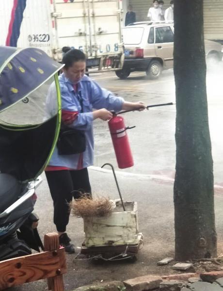 5 月 25 日,湘潭雨湖区亚华花园小区附近,公交车司机冯建正用灭火器灭火。