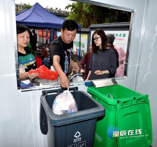(居民来到小区内的垃圾分类点,按照规定投放垃圾。资料图)