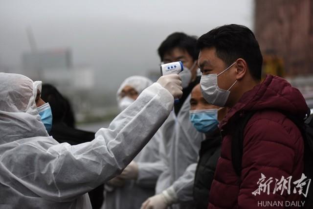2月9日,防疫工作人员在京港澳高速公路郴州站出口对进城司乘人员进行体温检测。