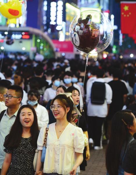 长沙黄兴路步行街,女孩带着气球开心地逛街。
